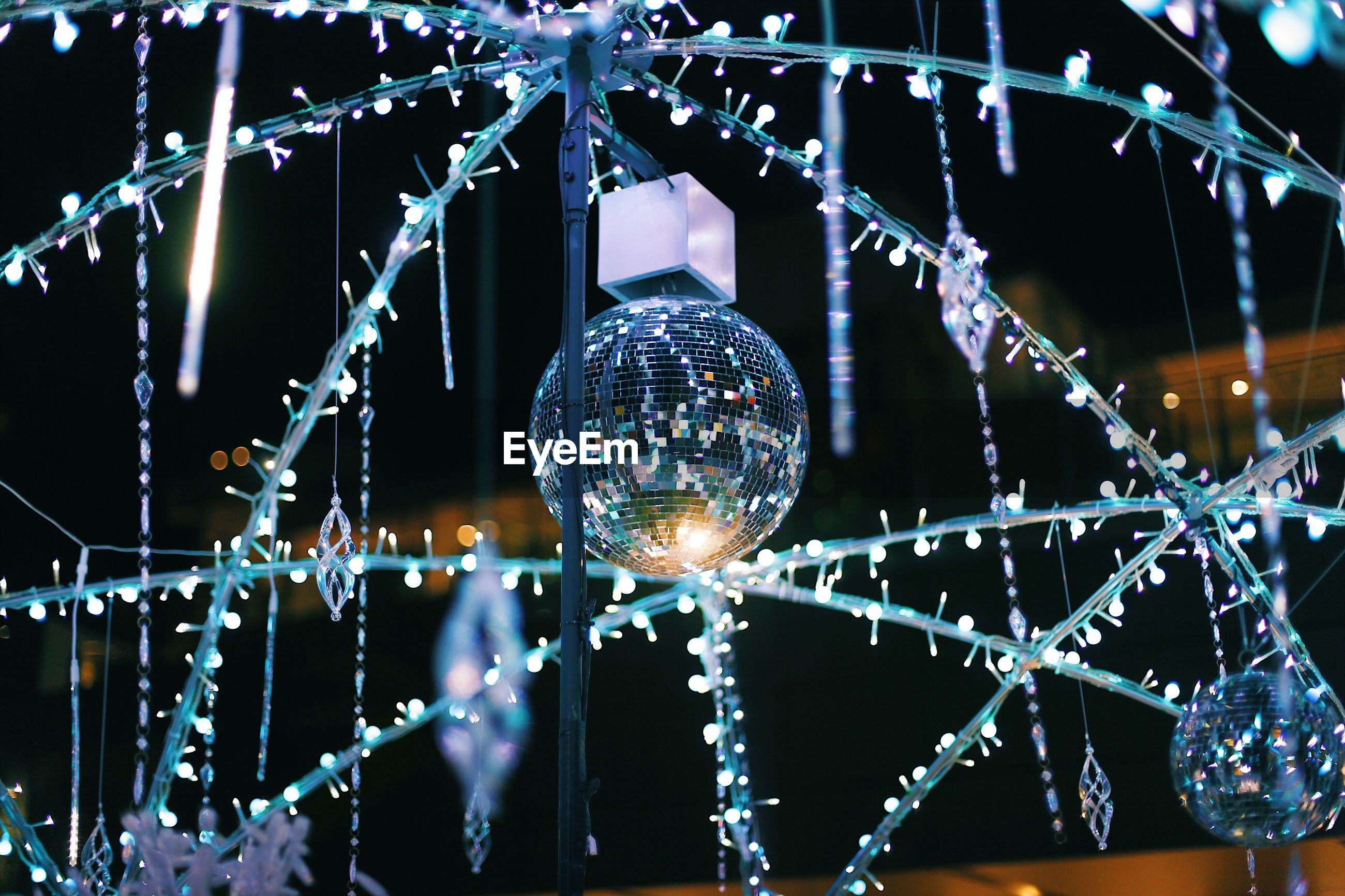 LOW ANGLE VIEW OF ILLUMINATED LANTERNS HANGING ON GLASS