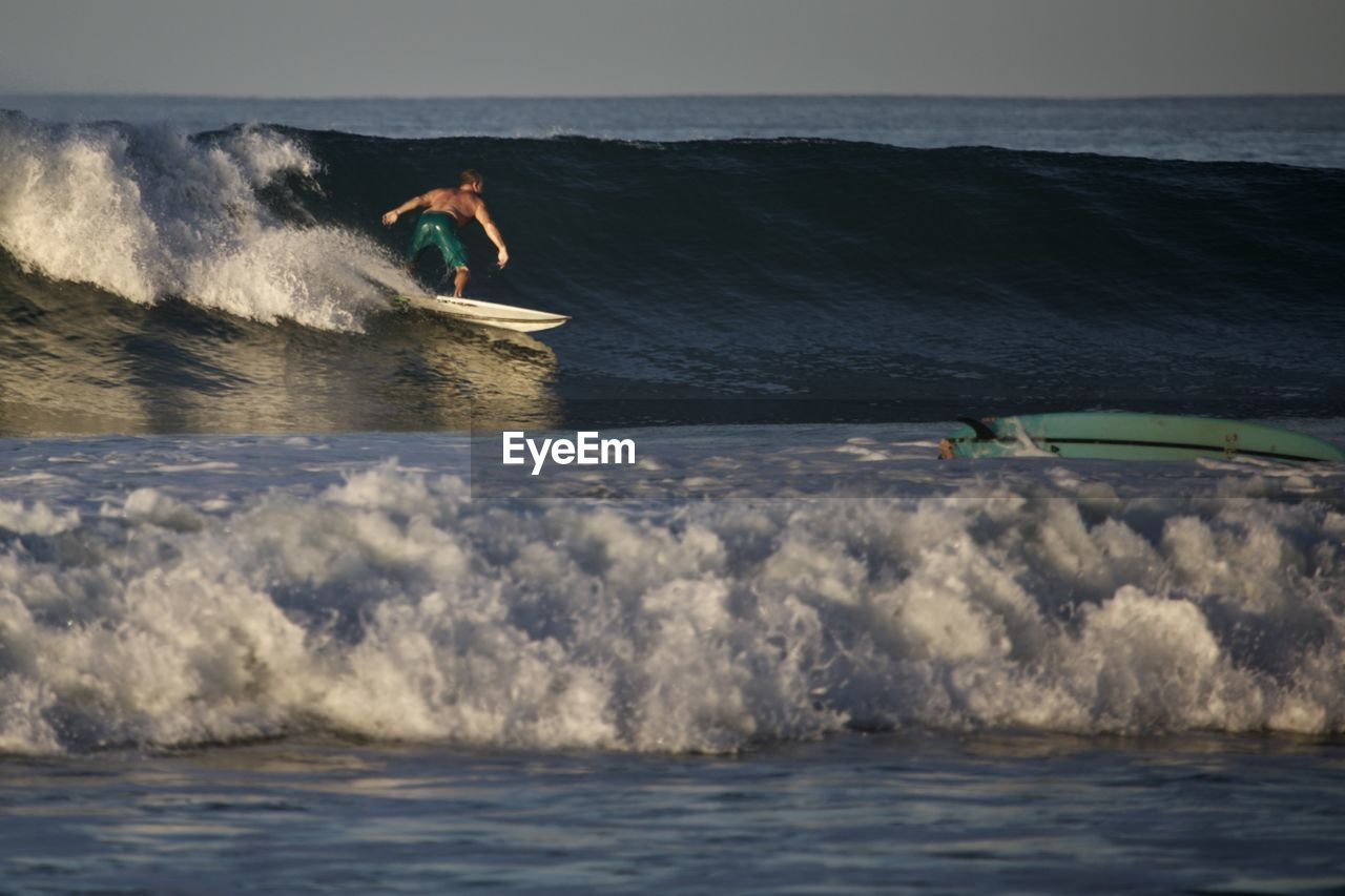 water, sea, aquatic sport, leisure activity, motion, sport, surfing, wave, real people, sky, people, nature, adventure, beauty in nature, waterfront, lifestyles, horizon over water, day, outdoors, power in nature