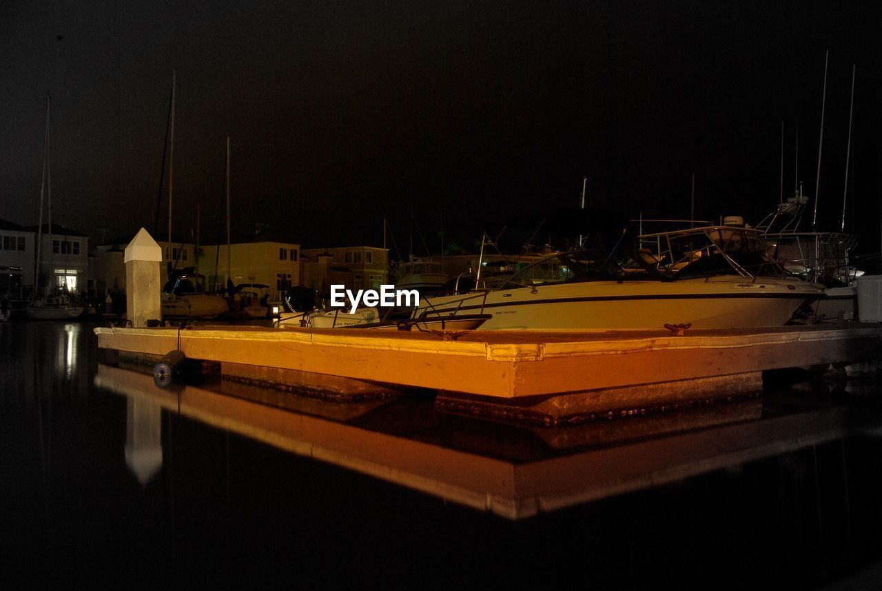 Boats moored on sea at night