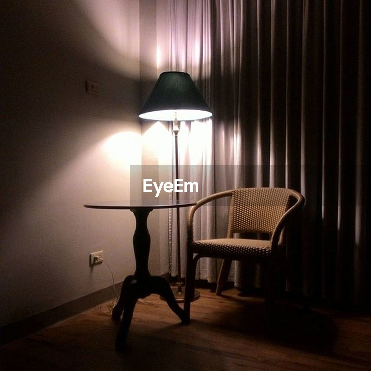 illuminated, lighting equipment, electric lamp, indoors, seat, light, chair, absence, no people, electric light, home interior, lamp shade, electricity, curtain, table, glowing, domestic room, wall, empty, furniture, side table