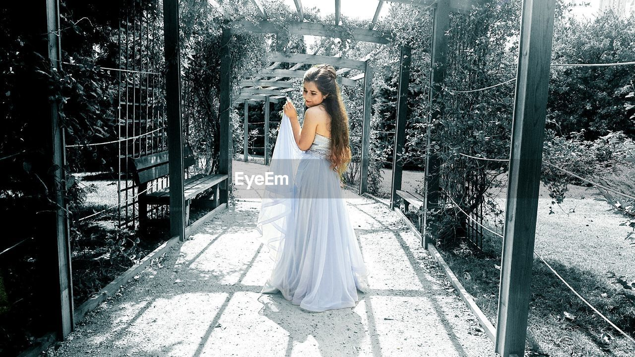 Young woman wearing dress standing at covered walkway