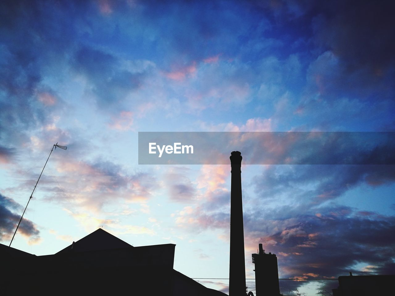 industry, built structure, smoke stack, sky, low angle view, silhouette, architecture, cloud - sky, chimney, building exterior, factory, outdoors, sunset, no people, day