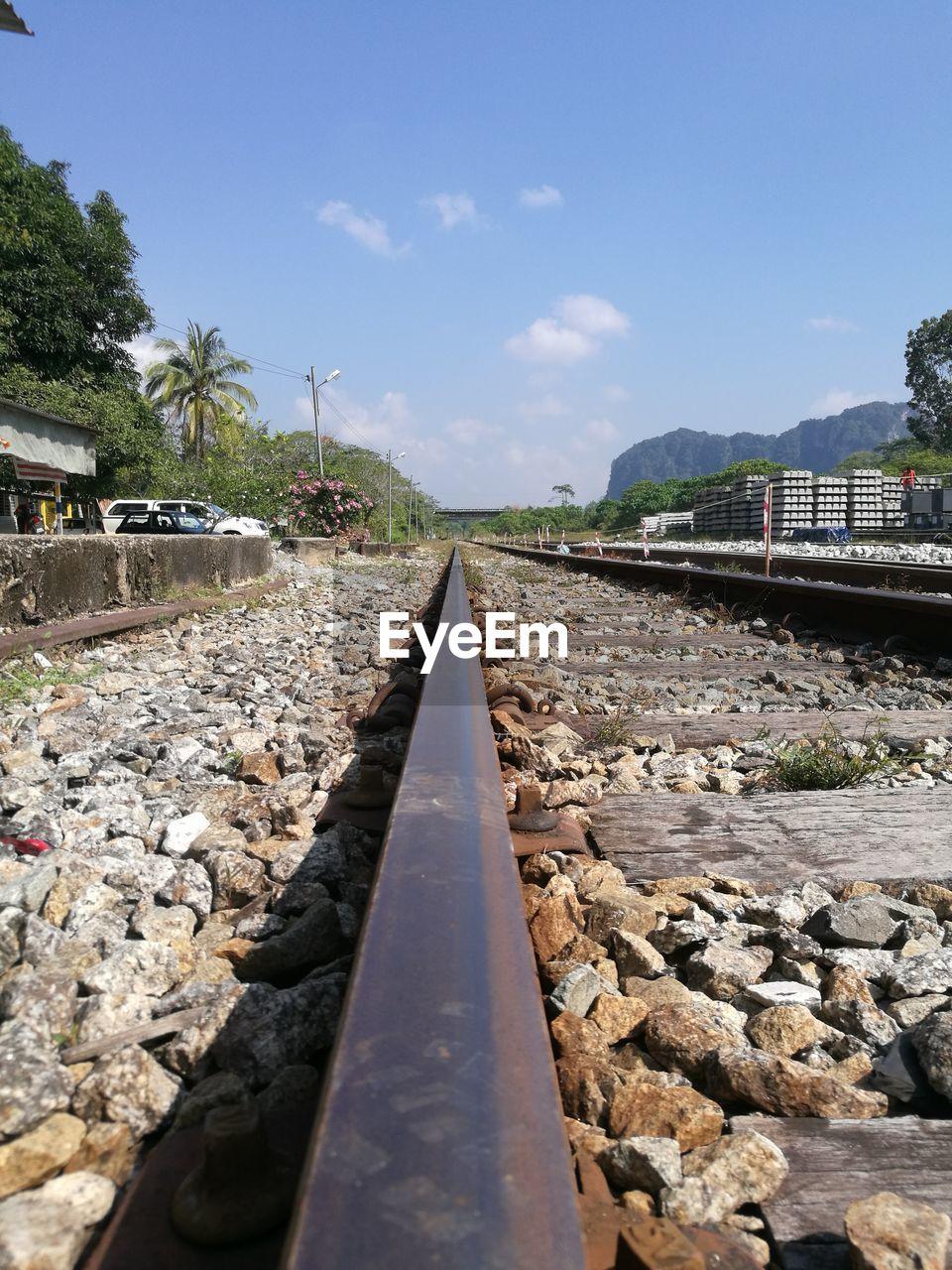 railroad track, rail transportation, transportation, stone - object, rock - object, day, no people, railroad tie, the way forward, outdoors, sky, public transportation, nature, tree