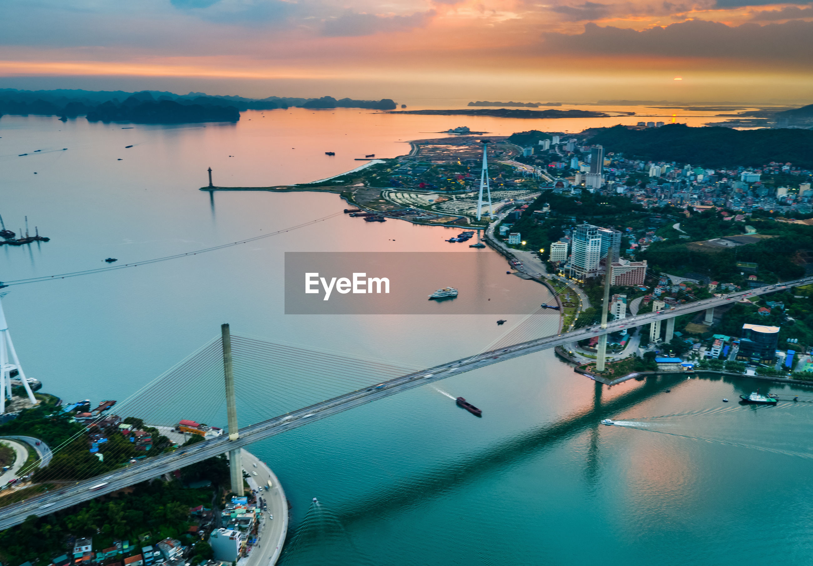 Aerial view of bridge over bay in city during sunset