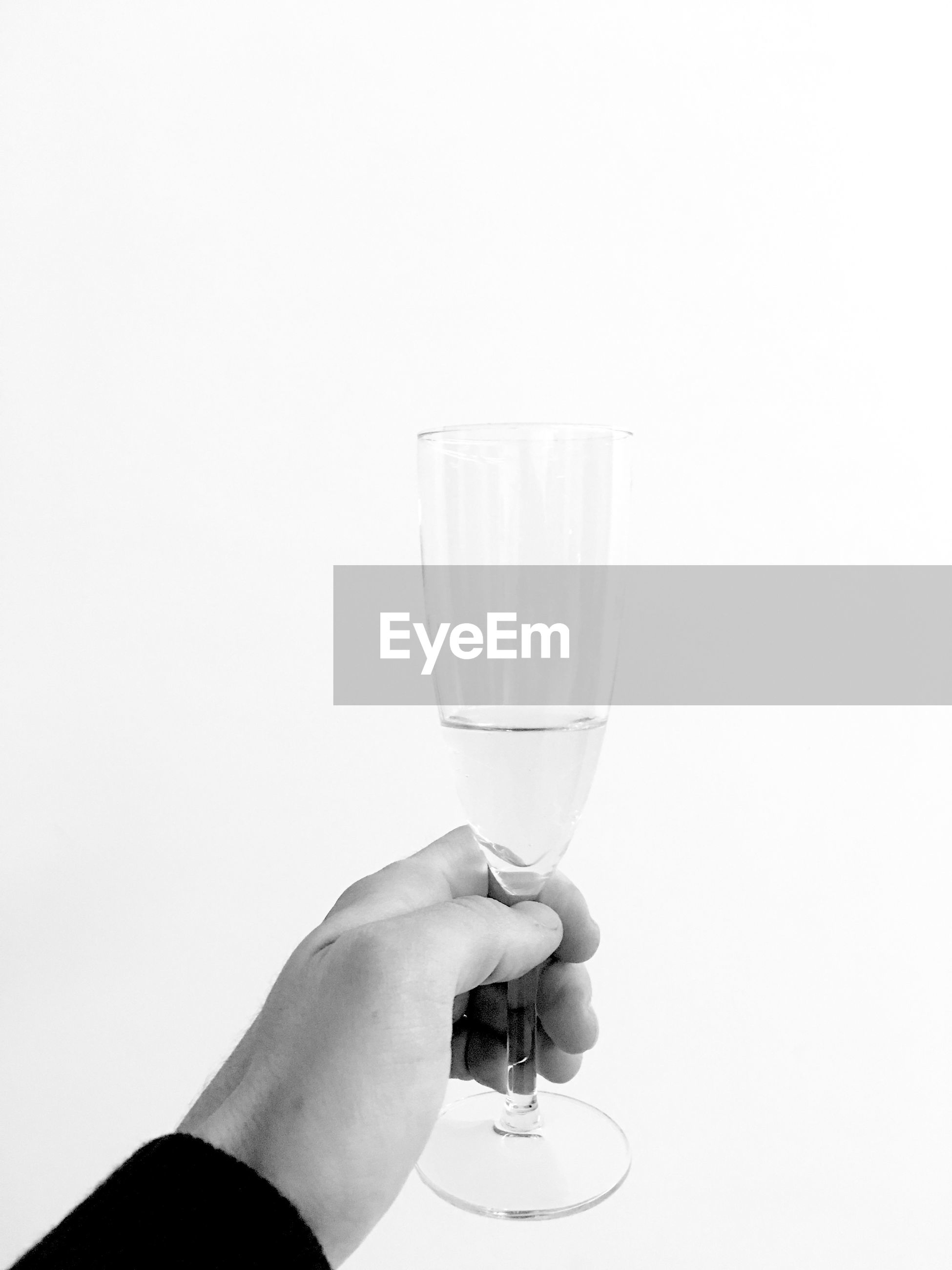 Cropped image of hand holding wineglass against white background