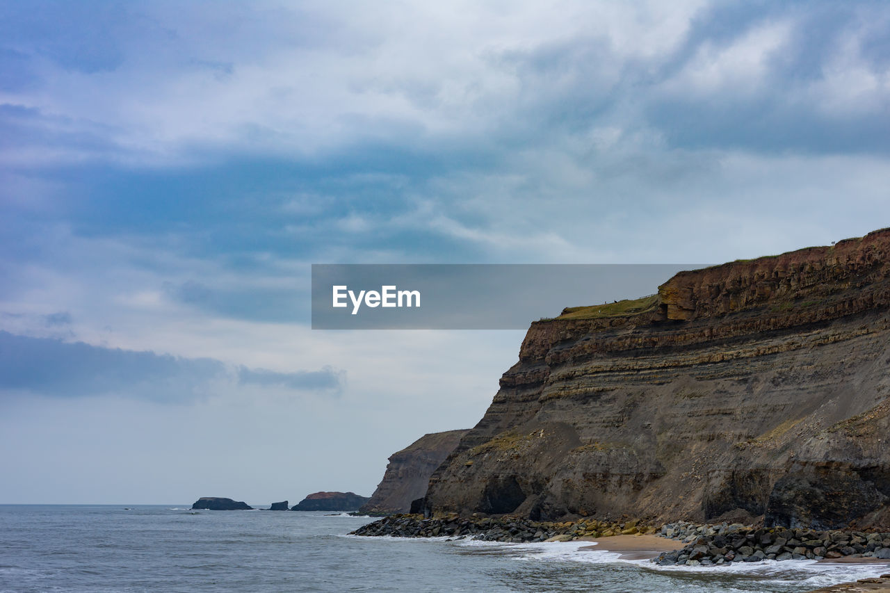 sky, sea, cloud - sky, water, beauty in nature, scenics - nature, rock, nature, tranquil scene, land, day, cliff, rock formation, tranquility, waterfront, rock - object, no people, beach, non-urban scene, horizon over water, outdoors, formation