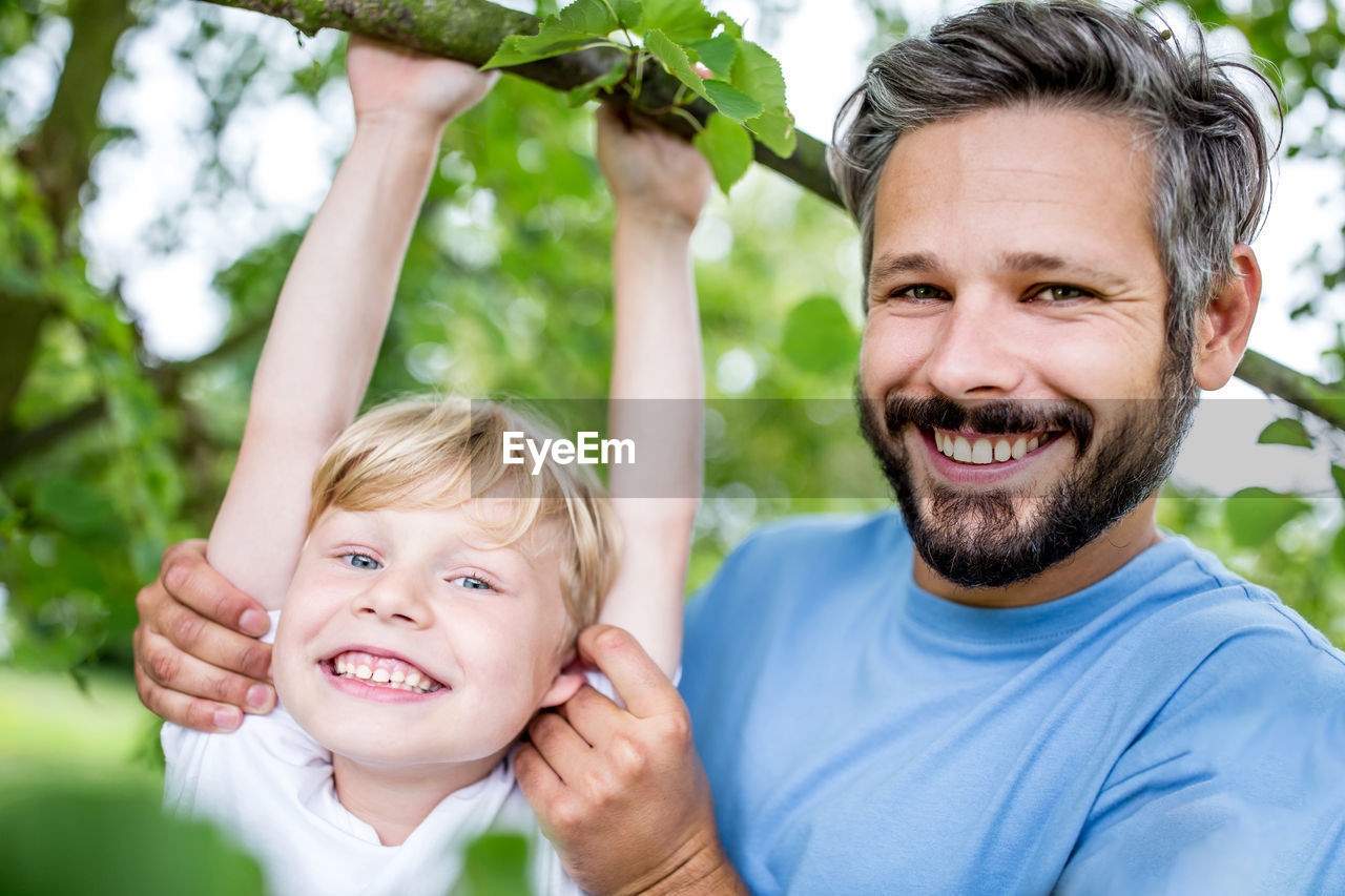 Portrait Of Smiling Father And Son At Park