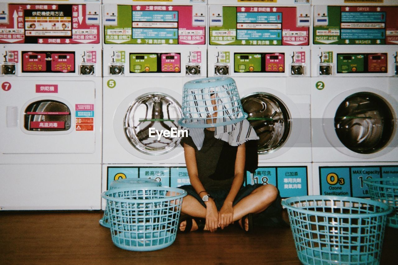 Young woman wearing laundry basket in laundromat