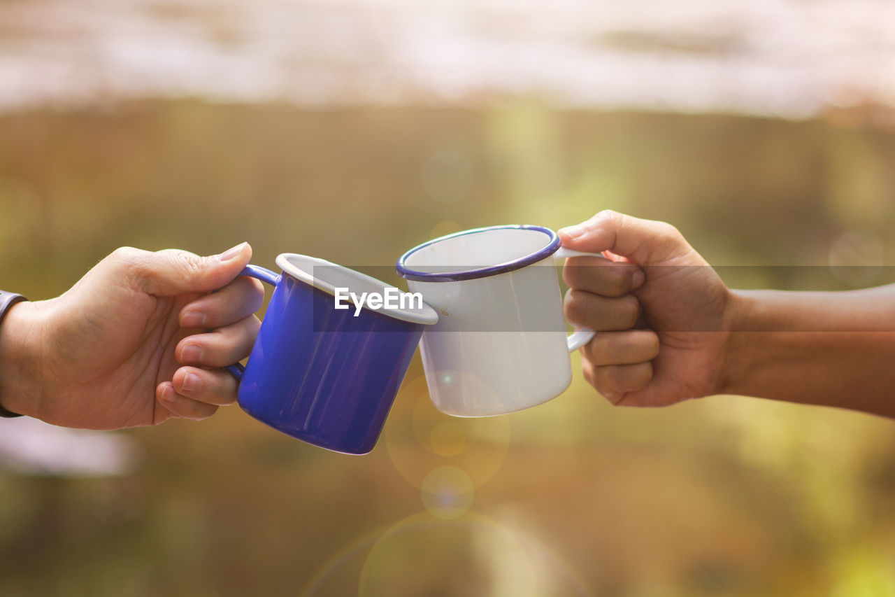 Cropped Image Of Hands Toasting Coffee Cup