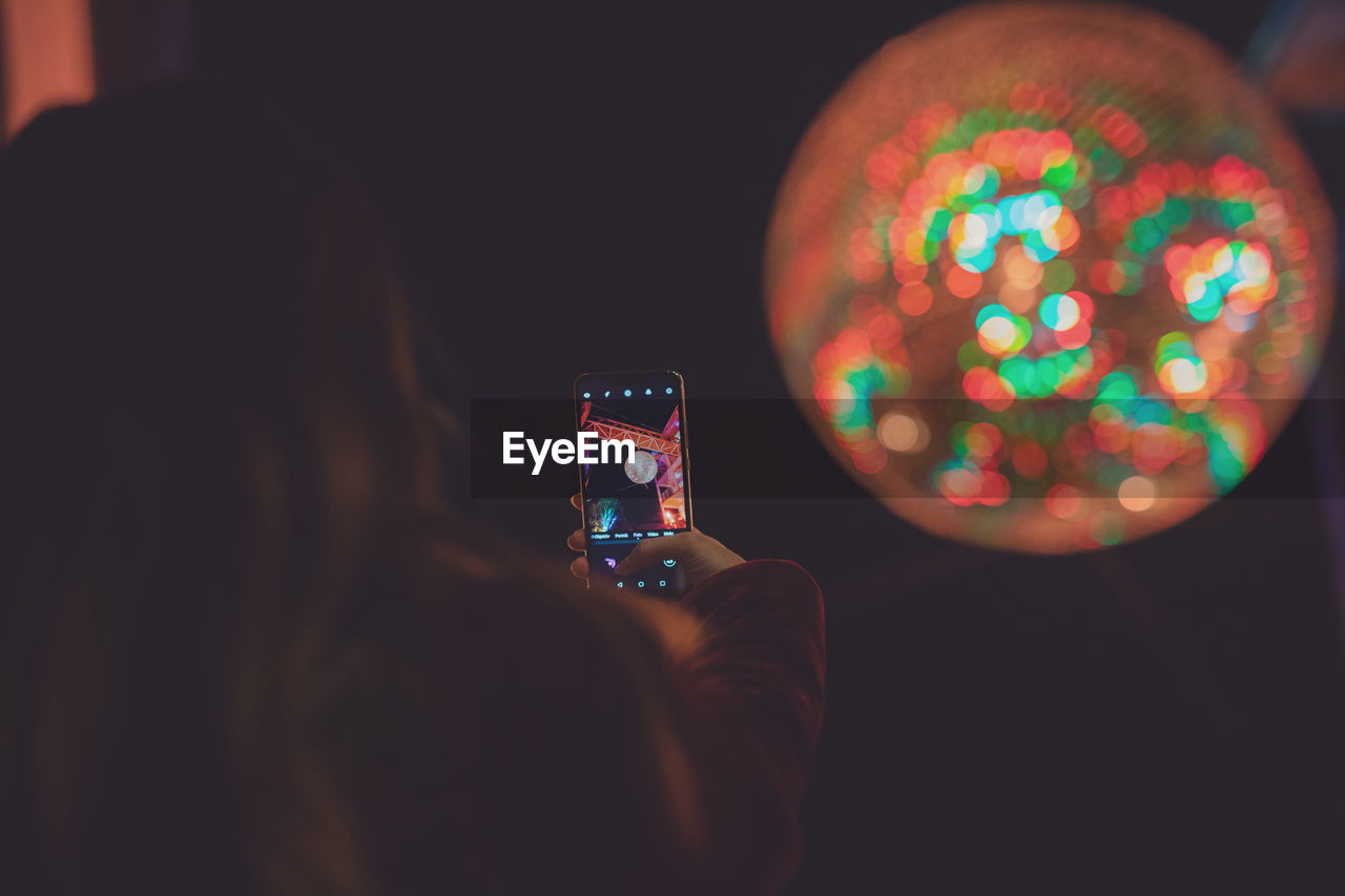 technology, mobile phone, smart phone, wireless technology, holding, screen, illuminated, portable information device, real people, communication, leisure activity, activity, selective focus, photographing, photography themes, one person, using phone, connection, device screen, night, hand