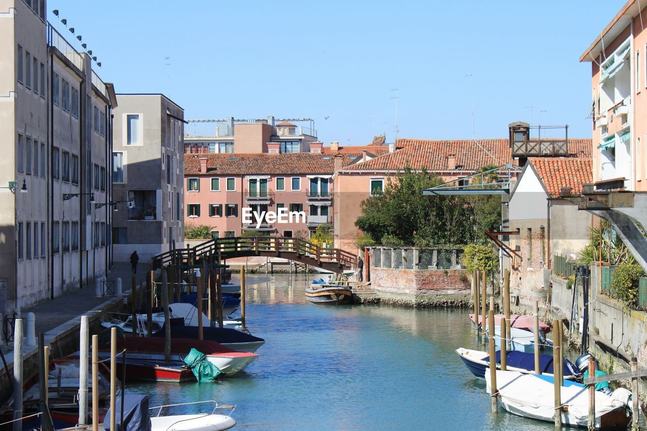 architecture, building exterior, built structure, water, nautical vessel, canal, transportation, building, residential district, mode of transportation, nature, sky, city, clear sky, bridge, waterfront, connection, day, moored, bridge - man made structure, no people, outdoors, wooden post