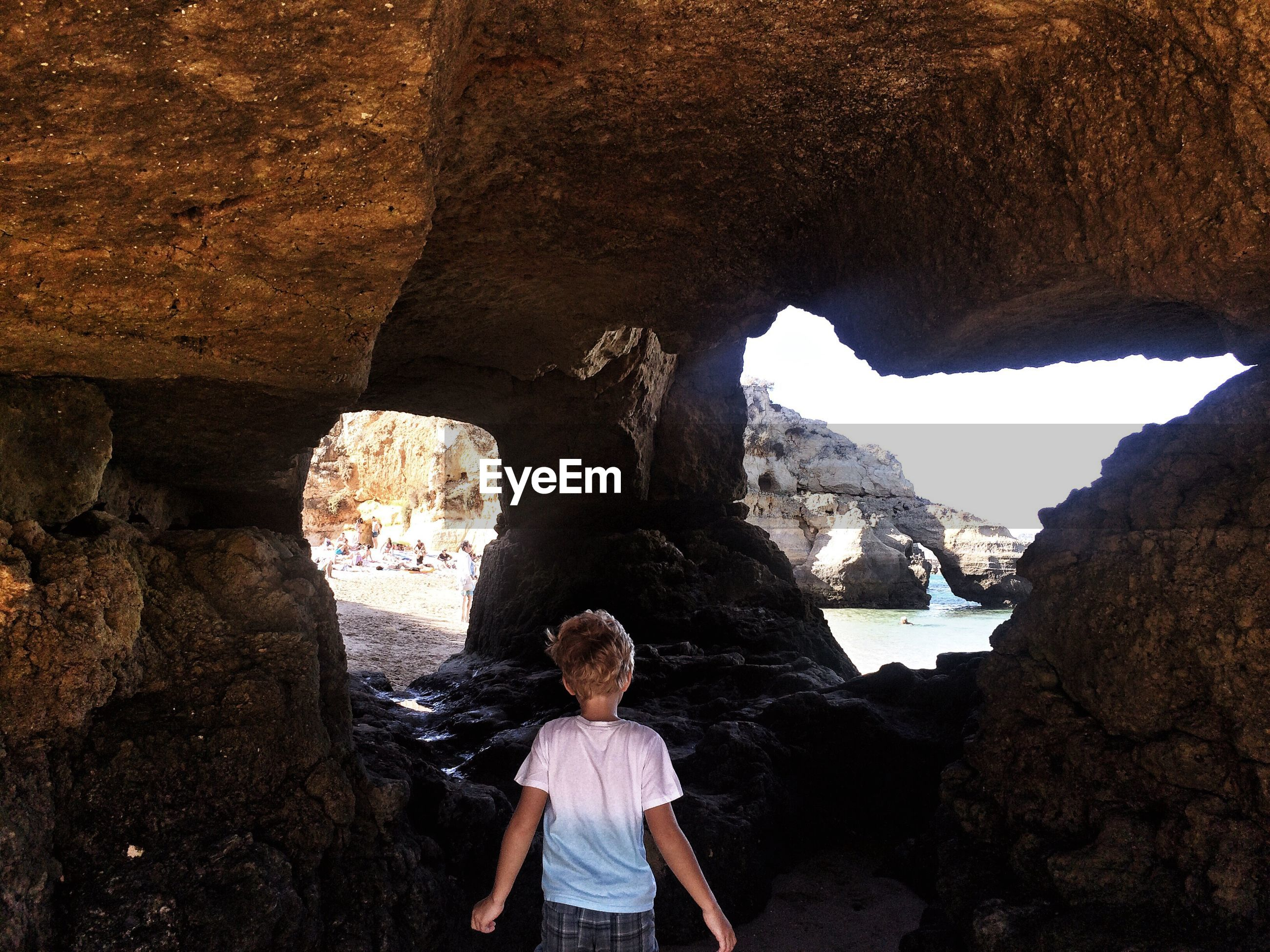 Rear view of boy standing in cave