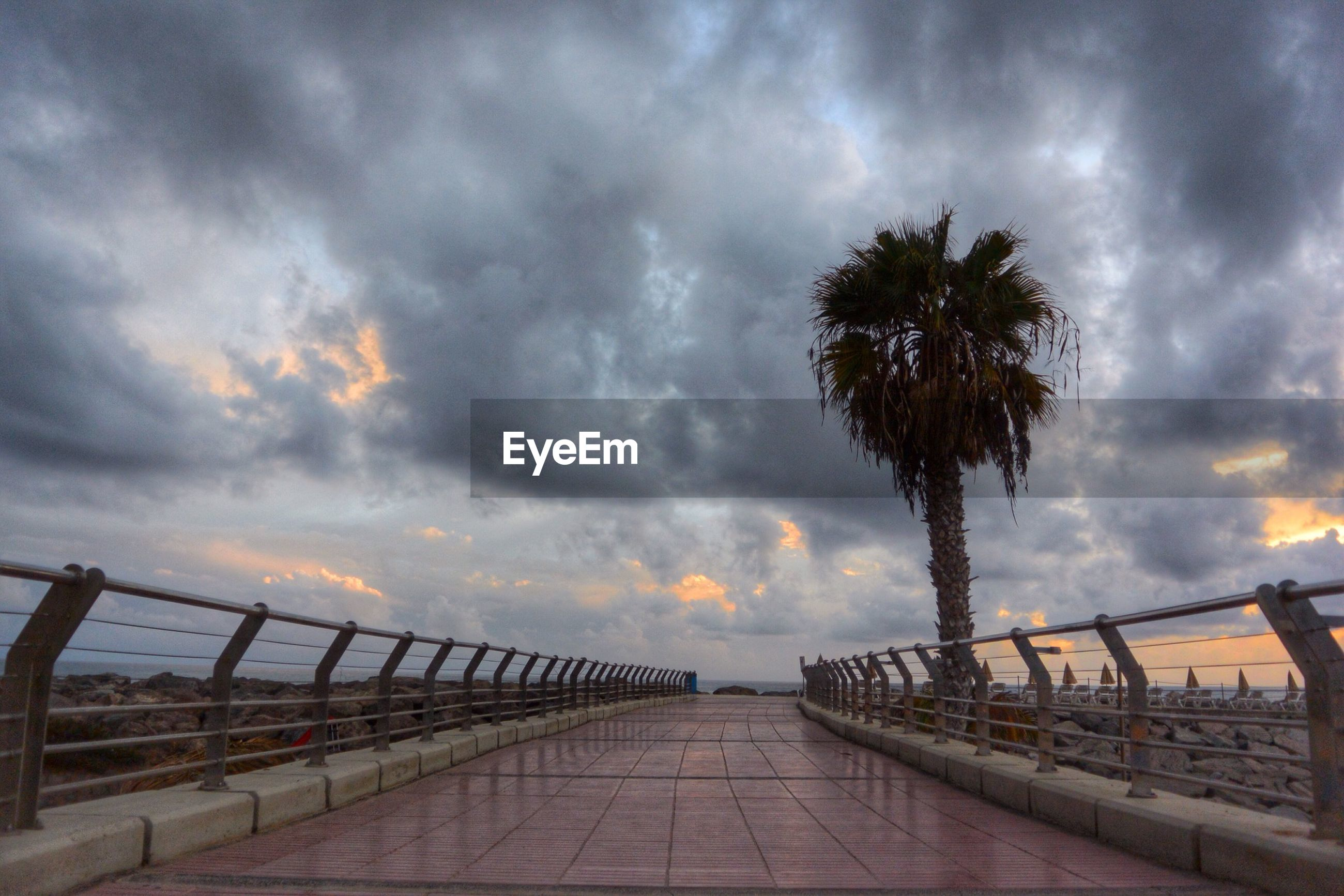 railing, cloud - sky, outdoors, sea, palm tree, sky, nature, no people, tree, beauty in nature, vacations, beach, storm cloud, day