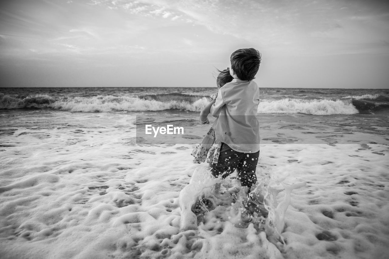 sea, real people, beach, horizon over water, sky, one person, water, nature, standing, beauty in nature, sand, outdoors, scenics, lifestyles, ankle deep in water, leisure activity, day, wave, full length, childhood, people