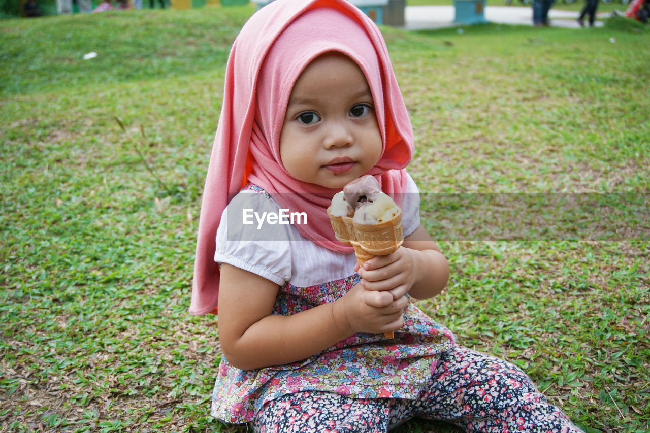 Portrait Of Girl Holding Ice Cream Cone On Field
