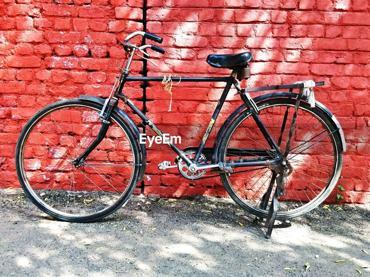 bicycle, transportation, brick wall, mode of transport, red, metal, outdoors, land vehicle, day, leaning, stationary, no people, built structure, architecture