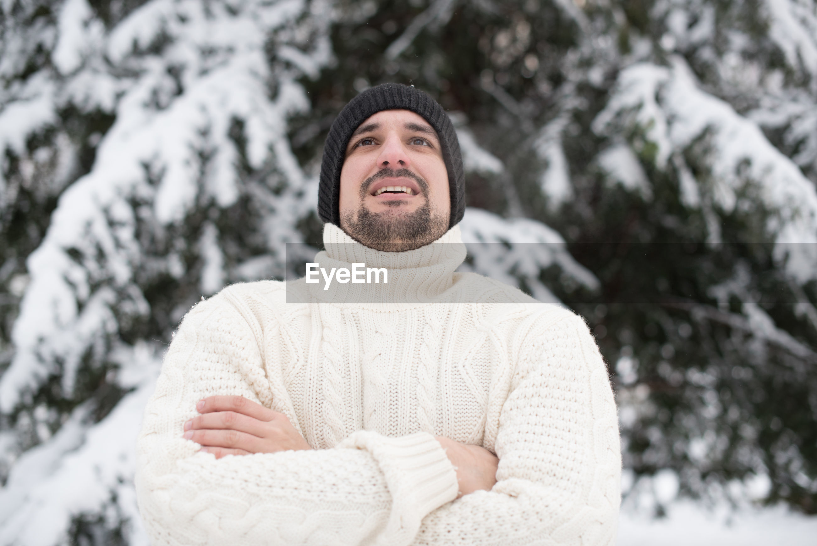 Portrait of young man against trees during winter