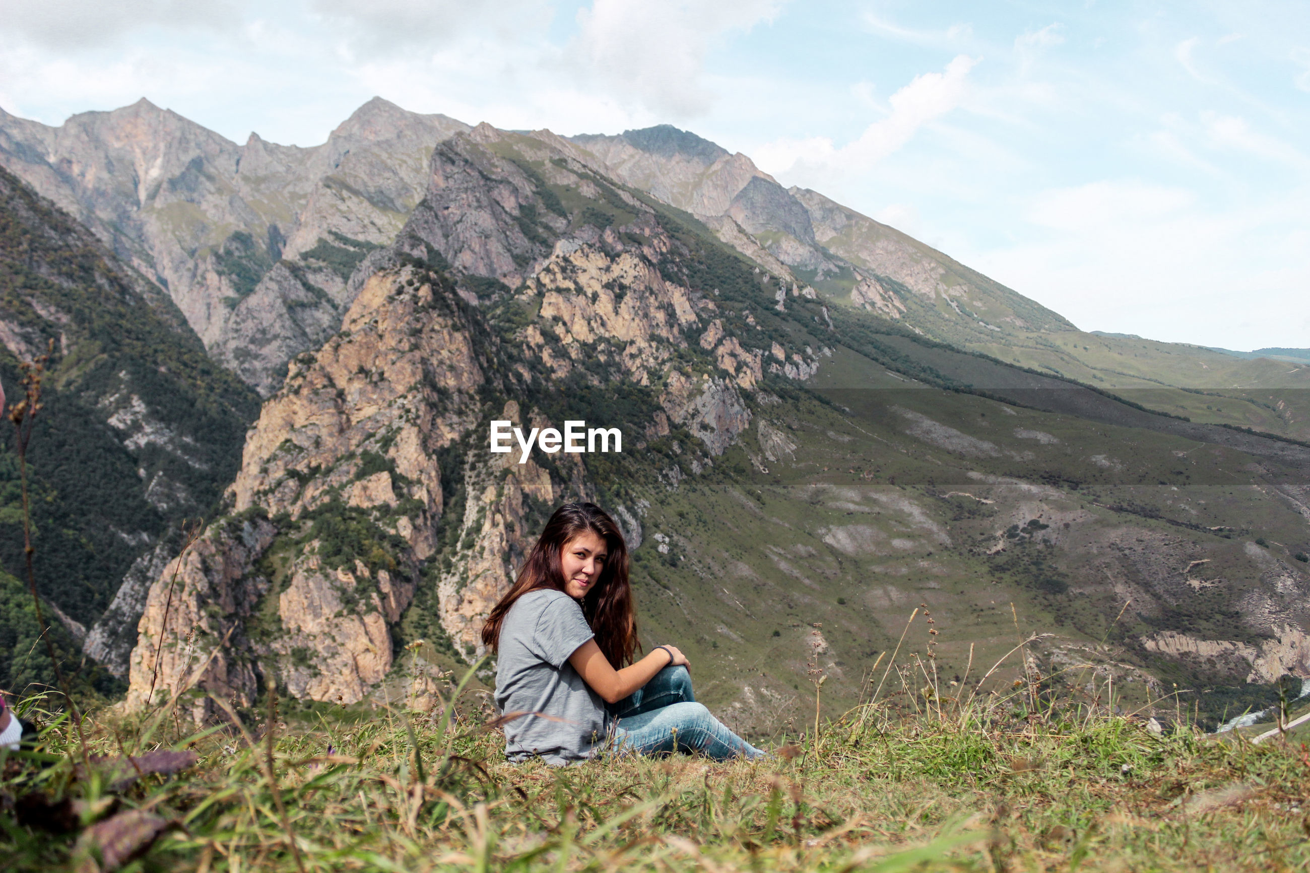 Side view of young woman sitting on field against mountain range