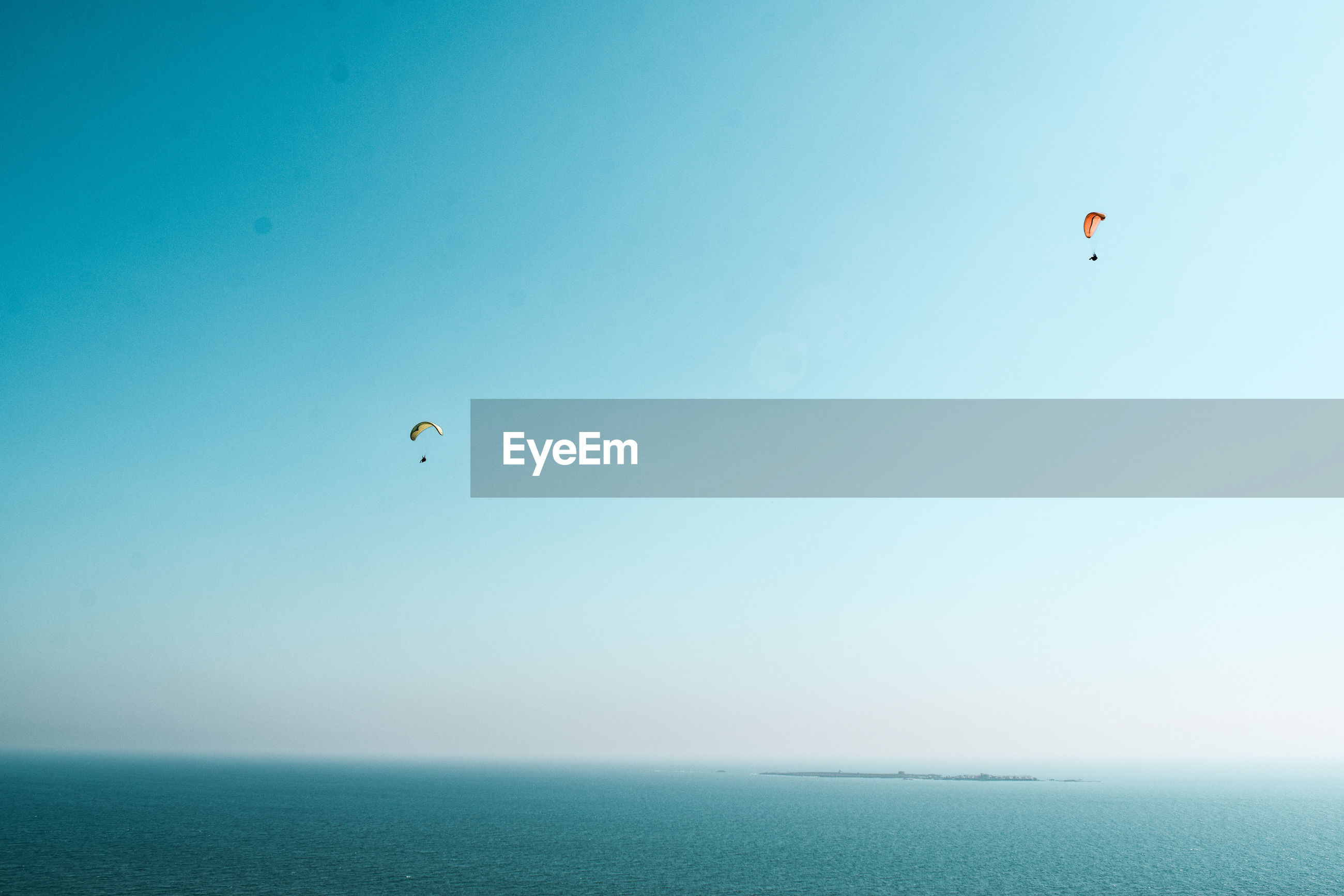 Scenic view of sea against clear sky with paragliders and islands