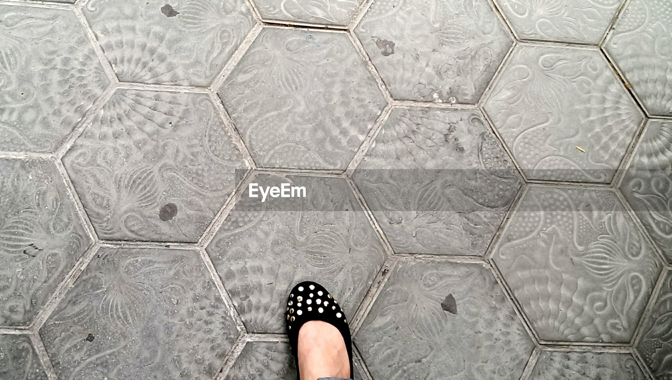 low section, person, personal perspective, shoe, standing, human foot, lifestyles, high angle view, footwear, unrecognizable person, flooring, tiled floor, leisure activity, pattern, directly above, men