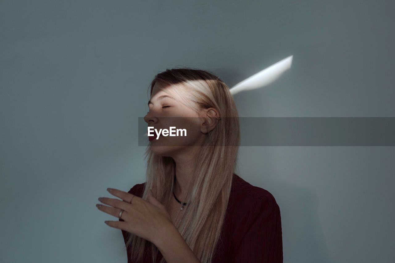 Woman With Closed Eyes Against Wall