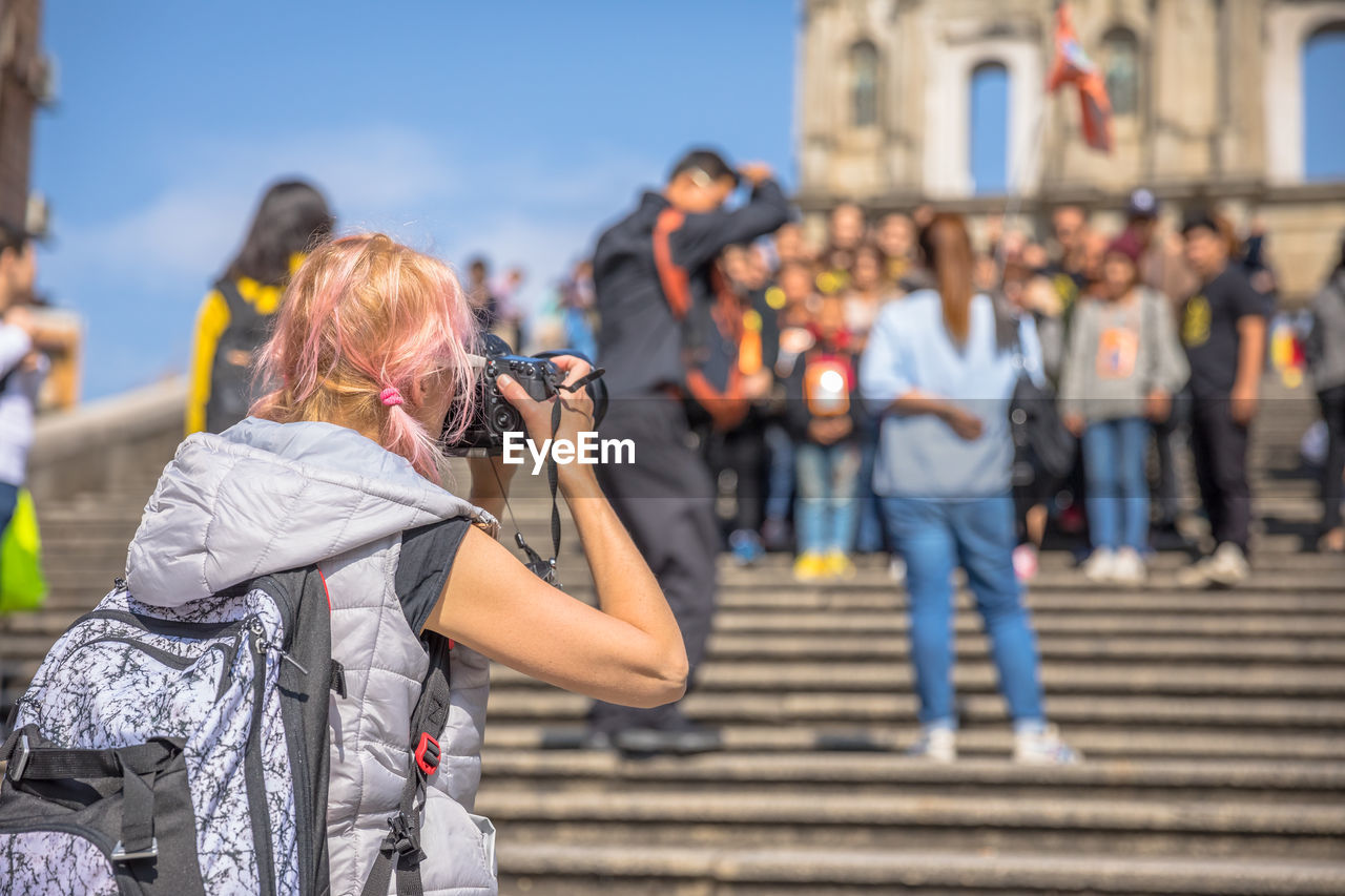 real people, photography themes, city, women, architecture, focus on foreground, leisure activity, lifestyles, photographing, group of people, technology, camera - photographic equipment, incidental people, people, day, street, holding, crowd, adult, outdoors, hairstyle