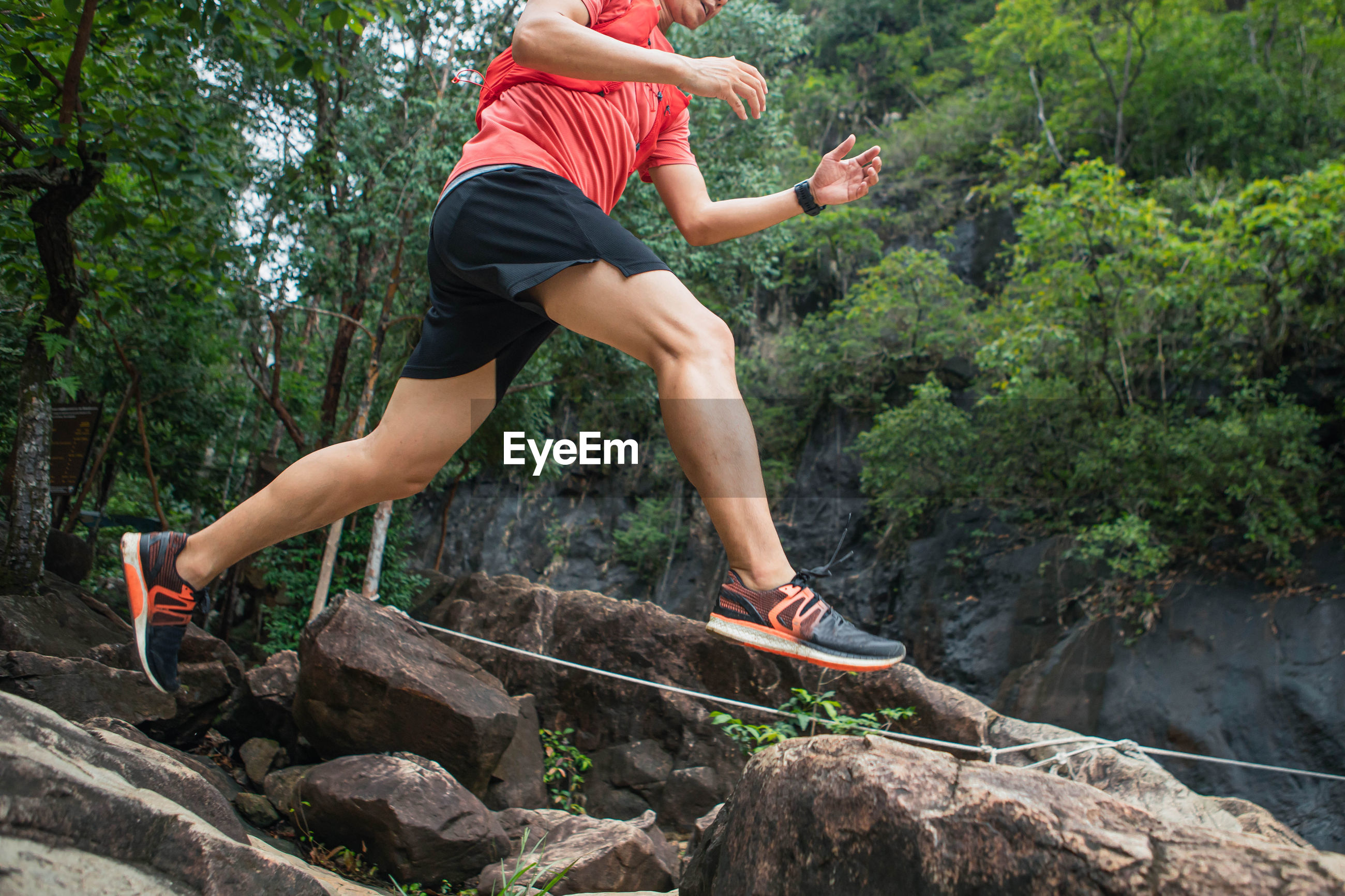 MAN JUMPING ON ROCK AT FOREST