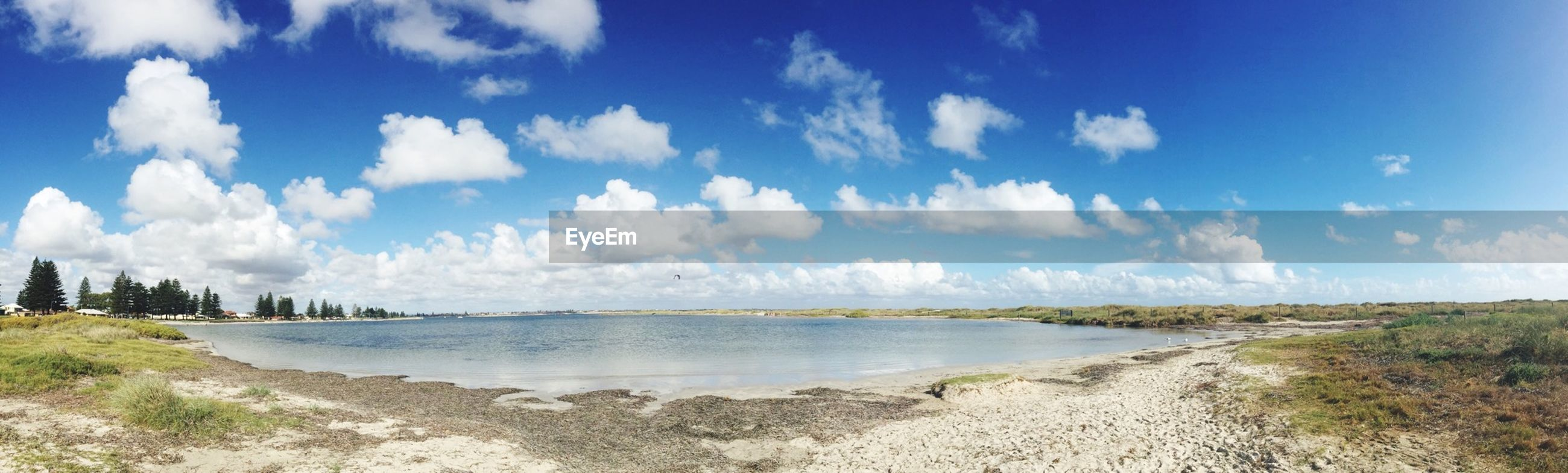 water, sky, tranquil scene, tranquility, scenics, beauty in nature, blue, nature, sea, cloud - sky, beach, cloud, shore, idyllic, panoramic, day, sunlight, grass, outdoors, non-urban scene