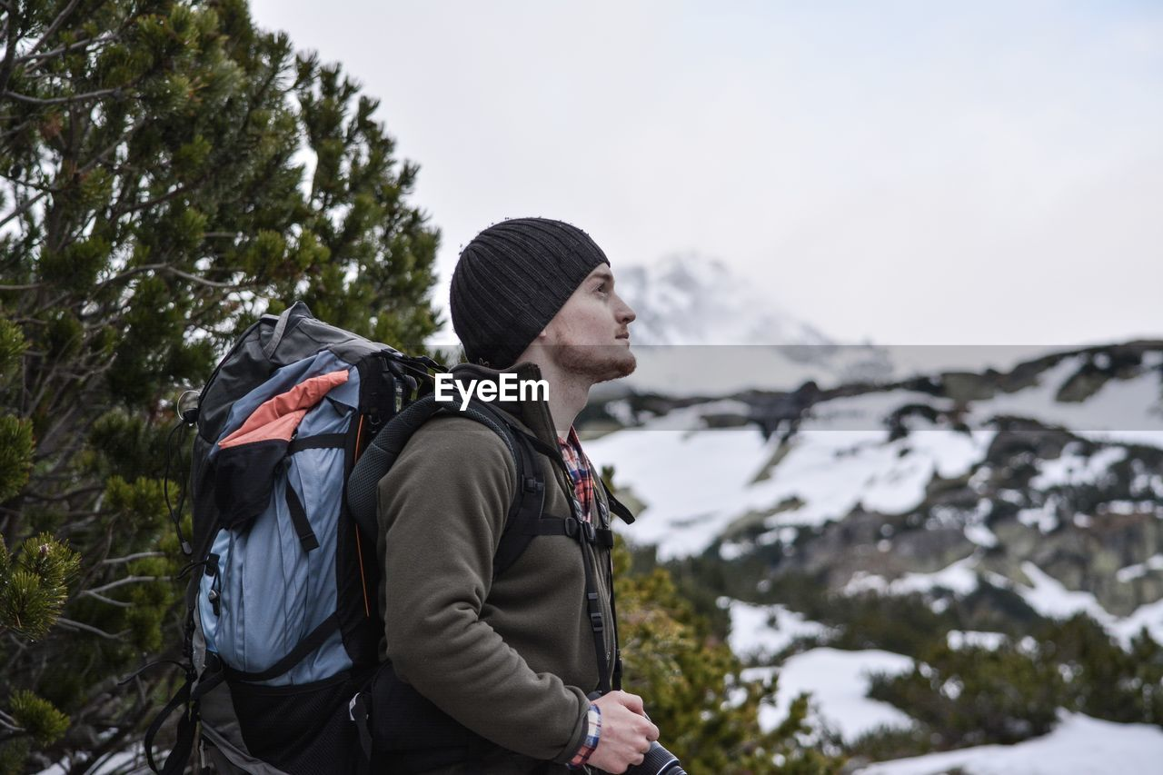 Man looking away against snowcapped mountains
