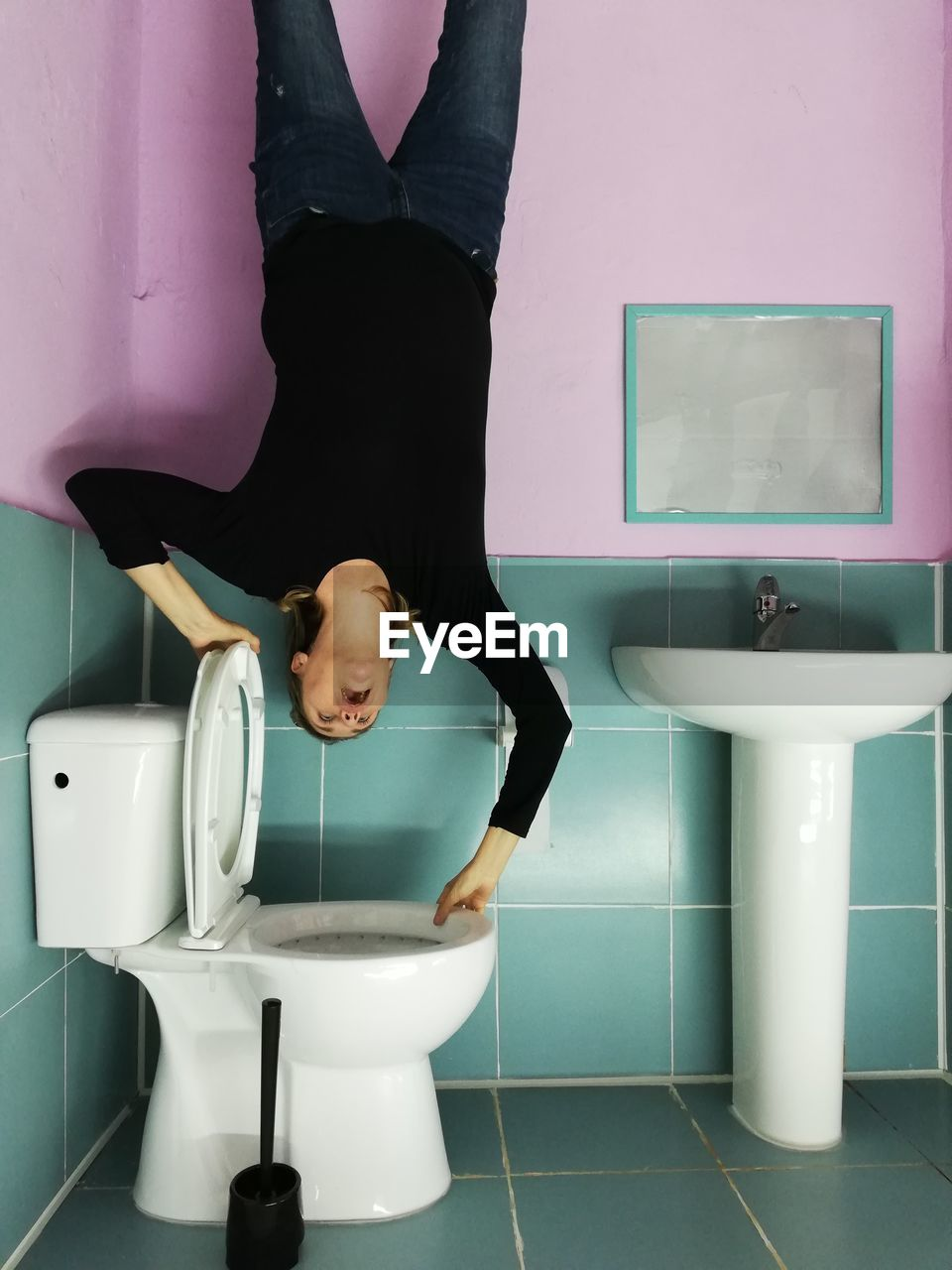 Woman upside down on toilet bowl in bathroom