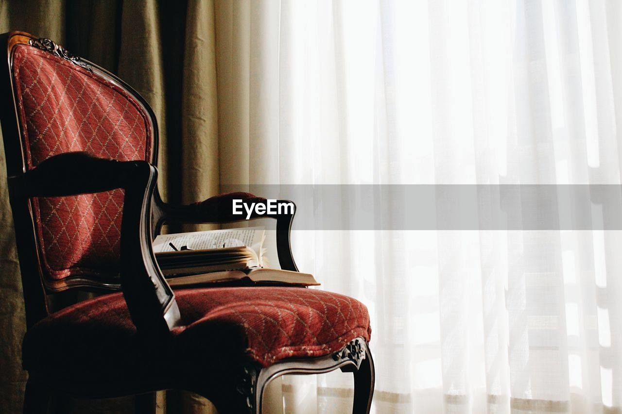 Books on armchair in against curtain in room