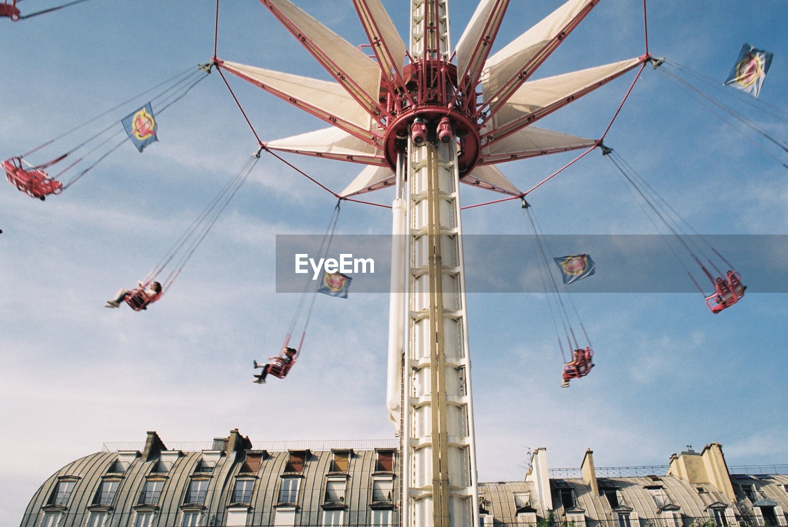 LOW ANGLE VIEW OF CAROUSEL AT AMUSEMENT PARK AGAINST SKY