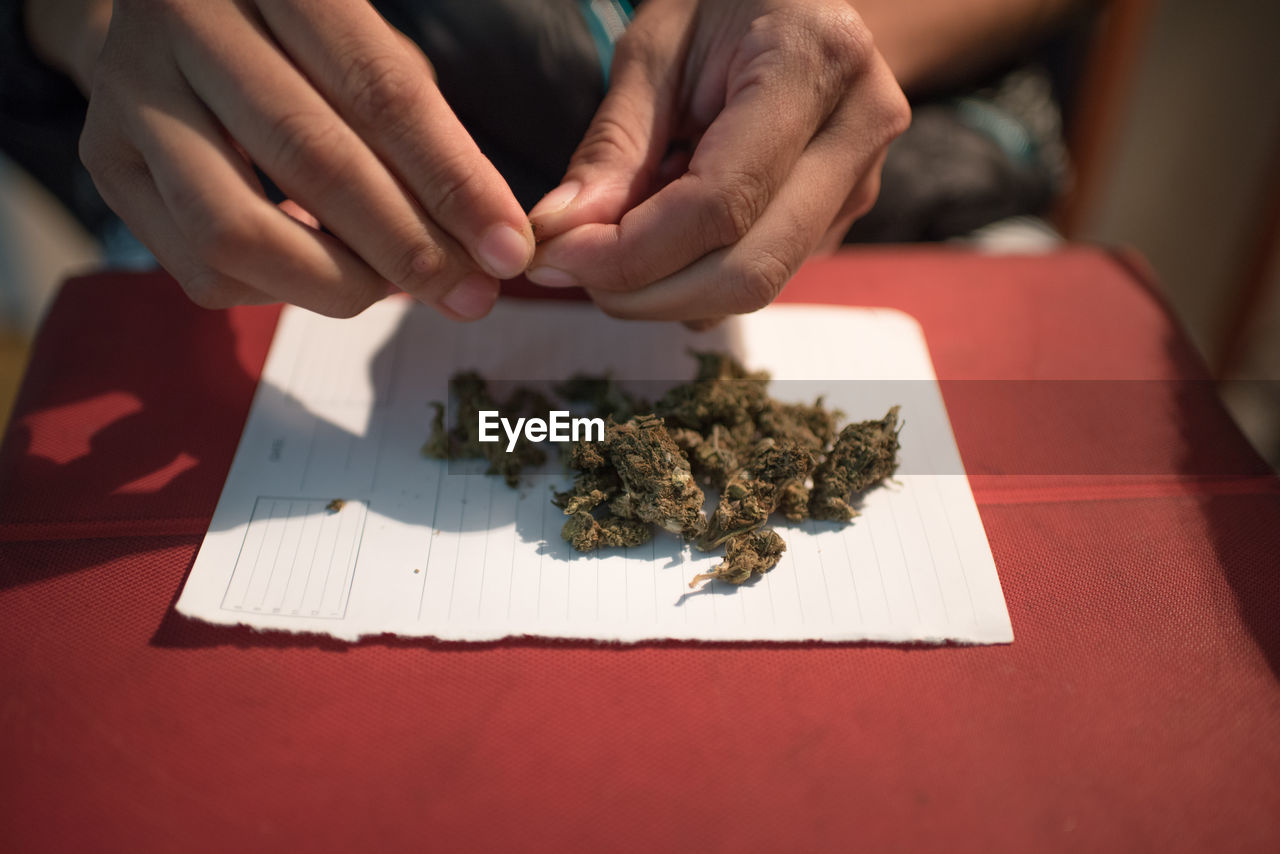 Cropped Hands Cleaning Marijuana Leaves On Table