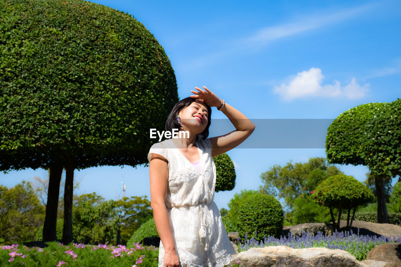 Smiling woman shielding eyes while standing in park
