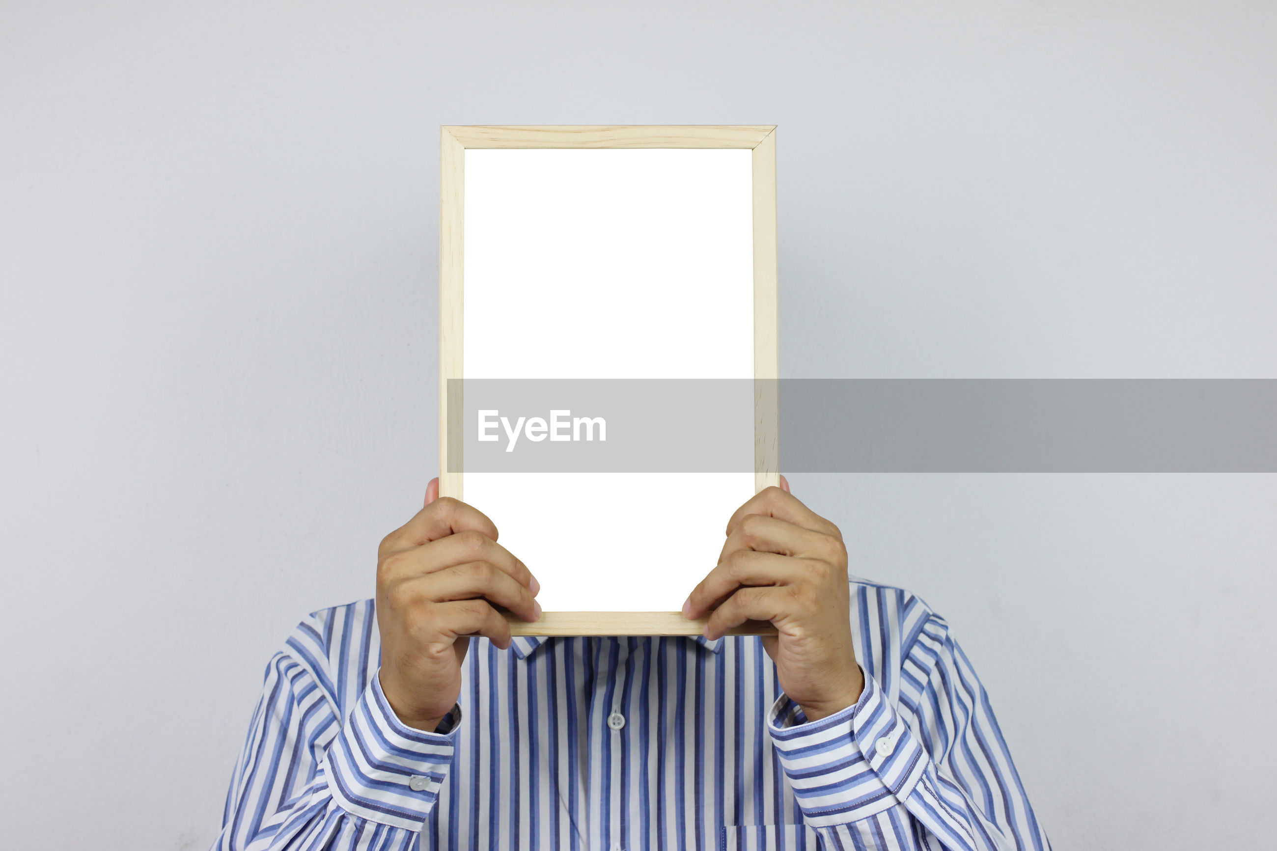 Close-up of man holding blank whiteboard against white background