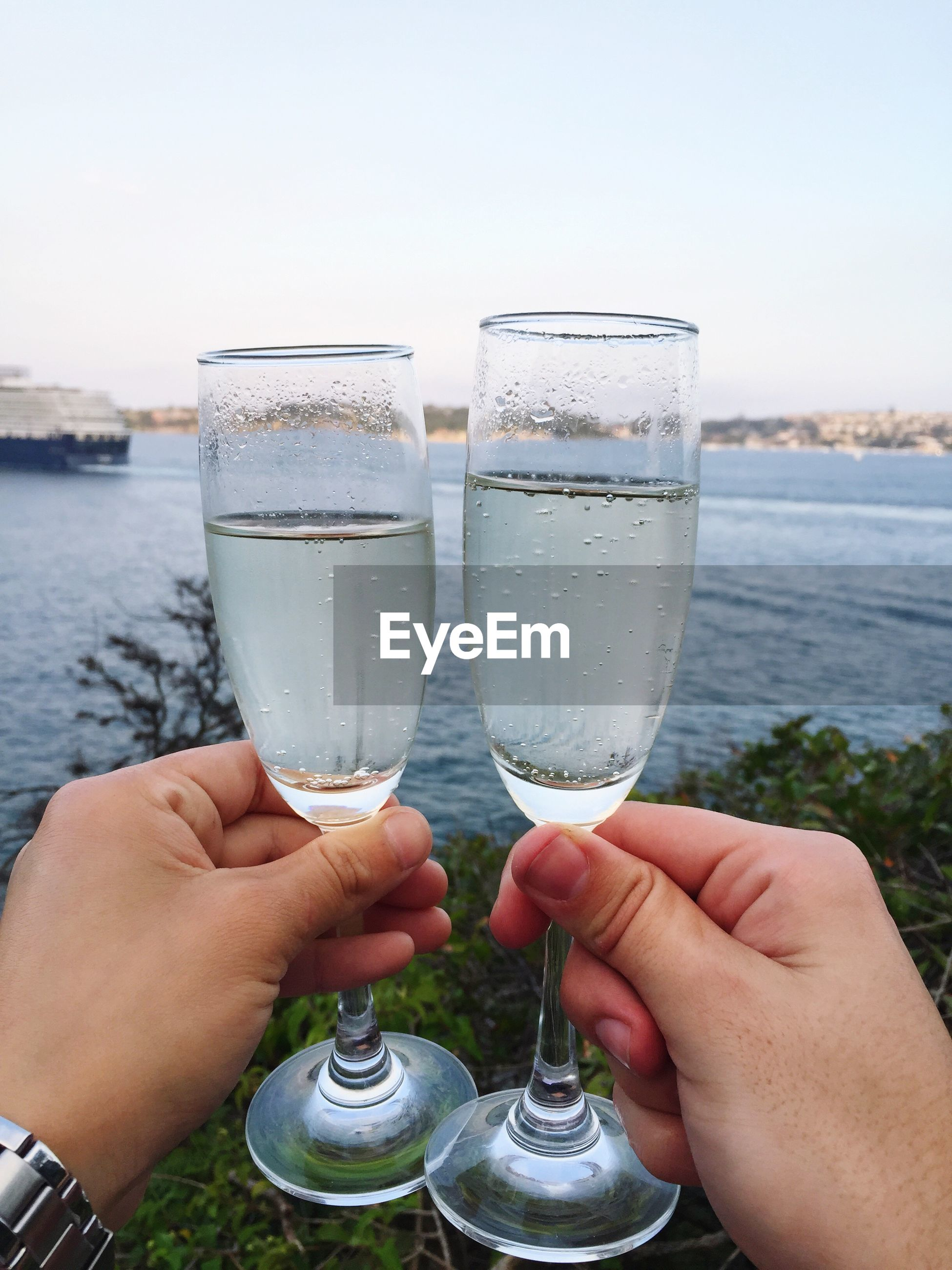 Cropped hands of man holding champagne flute against lake