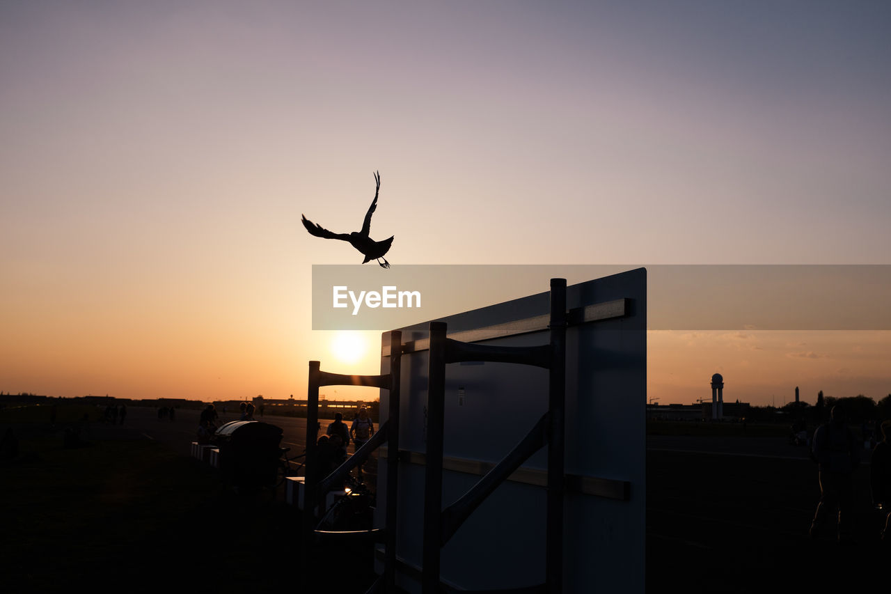 Silhouette bird flying over upside down table against sky during sunset