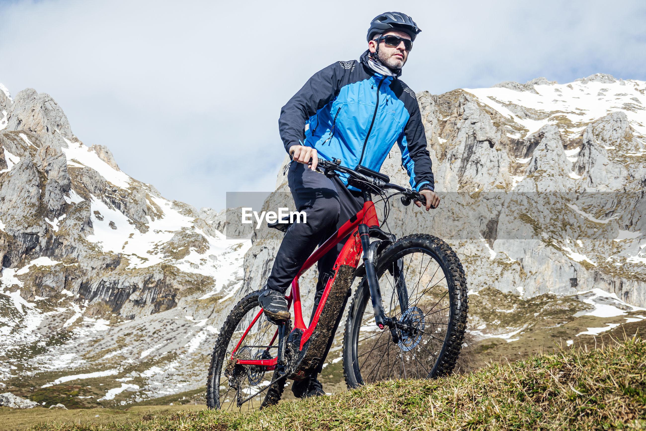 MAN RIDING BICYCLE ON MOUNTAINS
