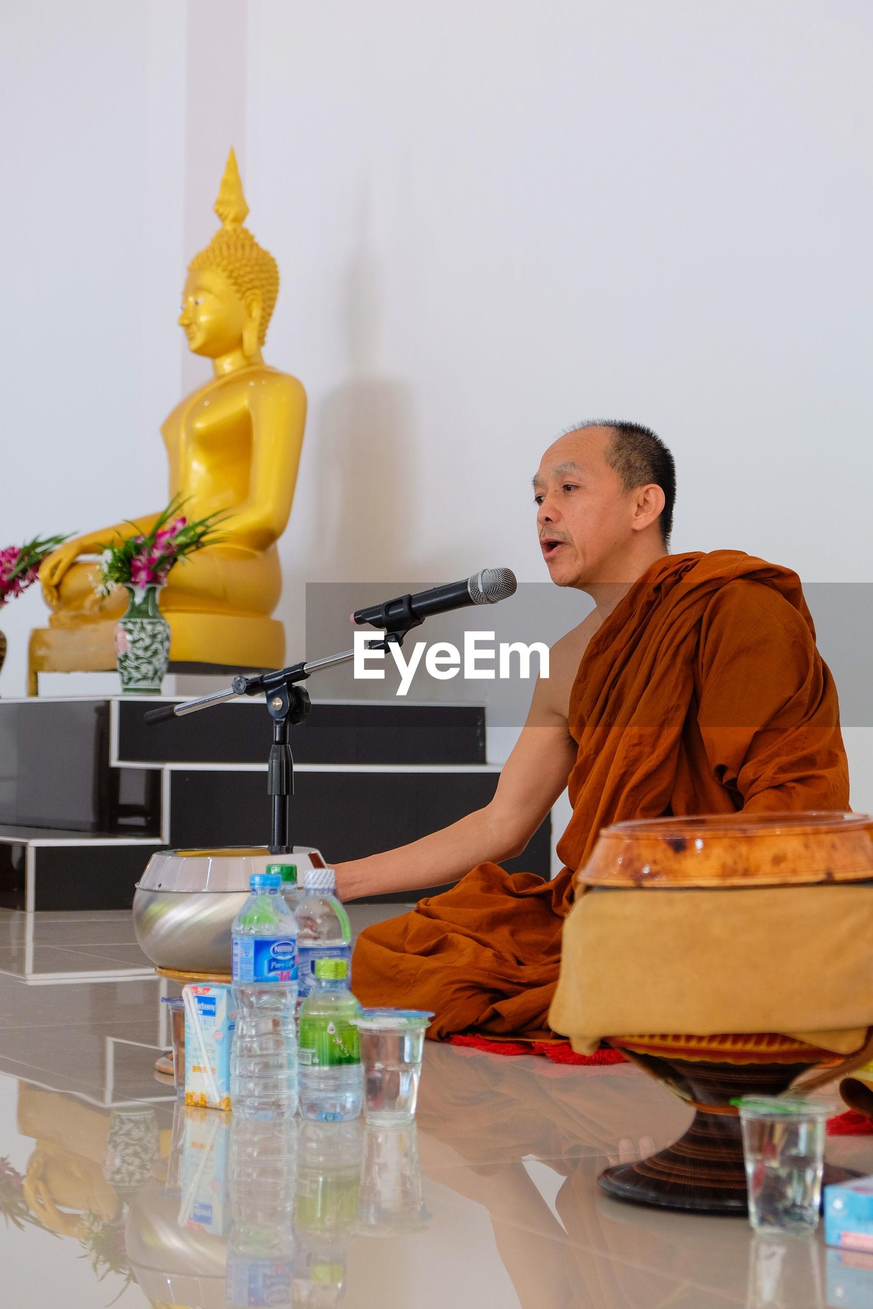 indoors, religion, buddha, spirituality, sitting, casual clothing, person, arrangement, domestic life, place of worship, large