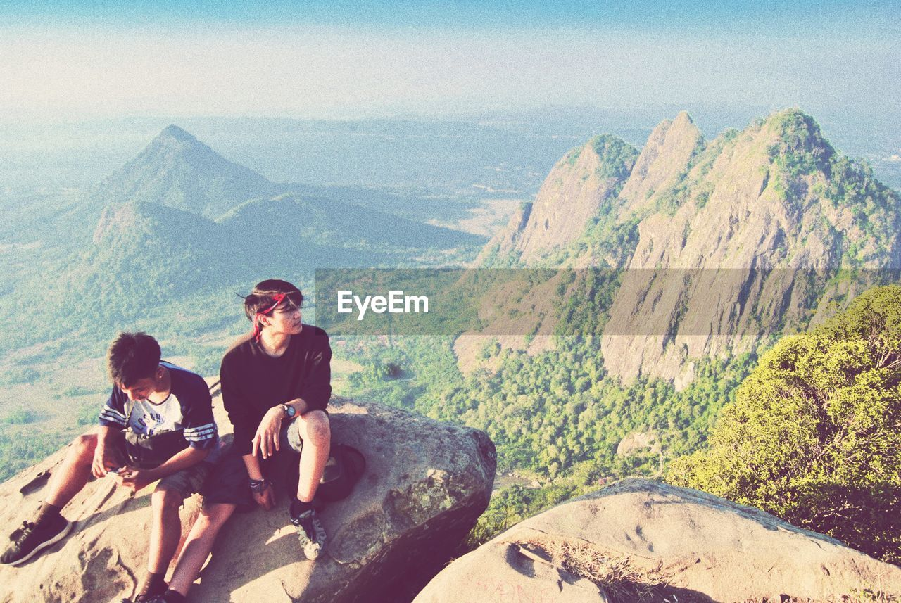 mountain, leisure activity, scenics - nature, togetherness, beauty in nature, nature, lifestyles, men, real people, rock, mountain range, group of people, people, day, family, sky, women, non-urban scene, tranquil scene, sitting, outdoors, sister