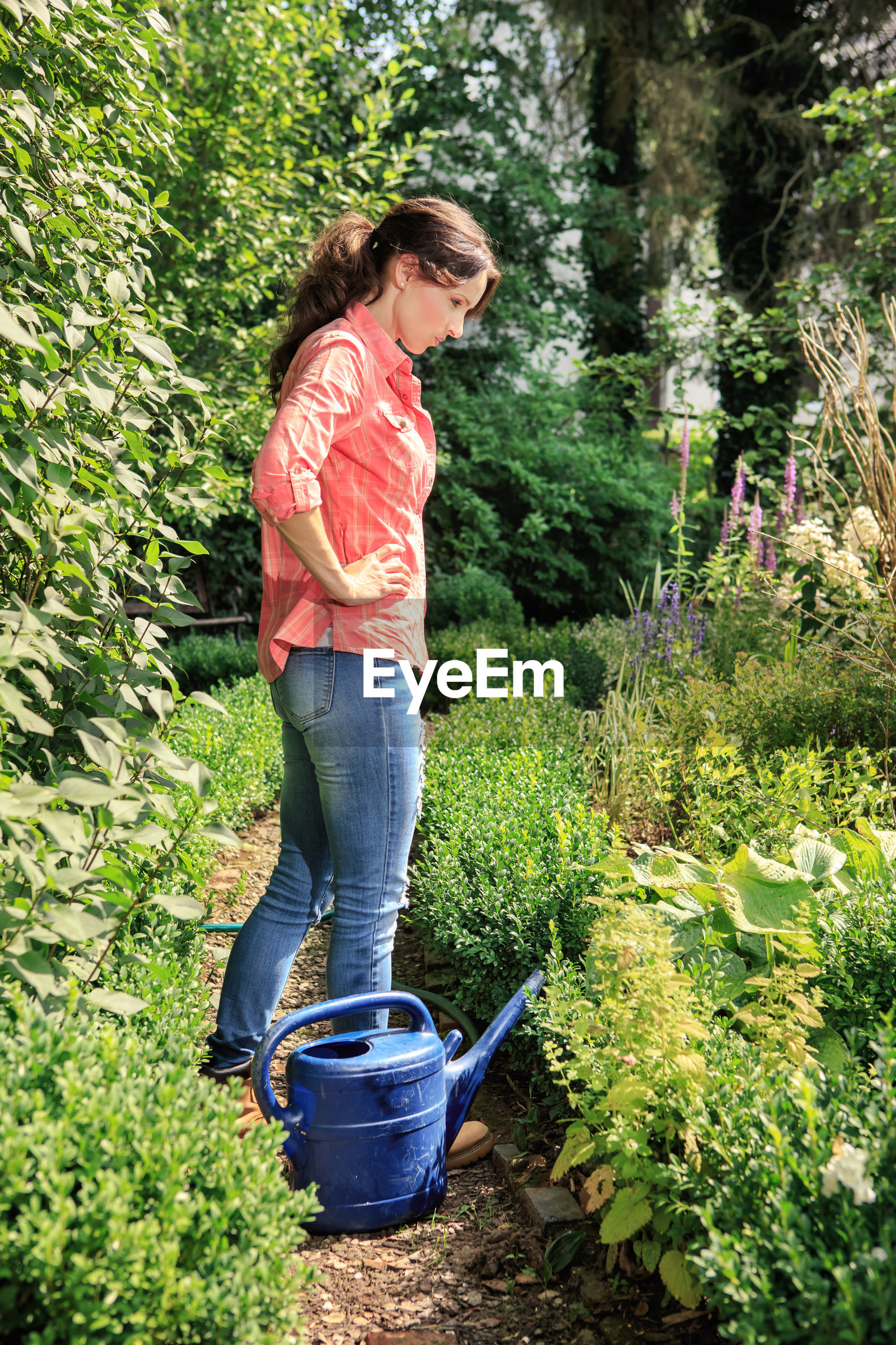 Side view of mid adult woman with watering can standing amidst plants in park