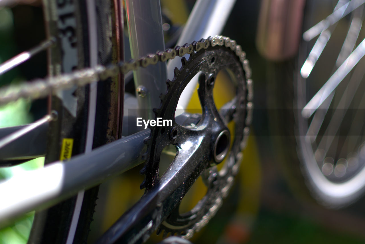 metal, bicycle, selective focus, no people, land vehicle, transportation, stationary, close-up, focus on foreground, mode of transportation, day, chain, wheel, pattern, outdoors, silver colored, equipment, security, shape, protection, spoke, tire