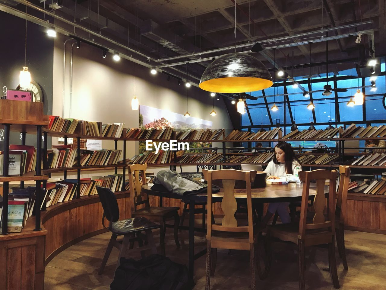 lighting equipment, indoors, business, illuminated, table, seat, real people, sitting, chair, restaurant, people, lifestyles, women, adult, ceiling, men, cafe, wood - material, electric lamp, light