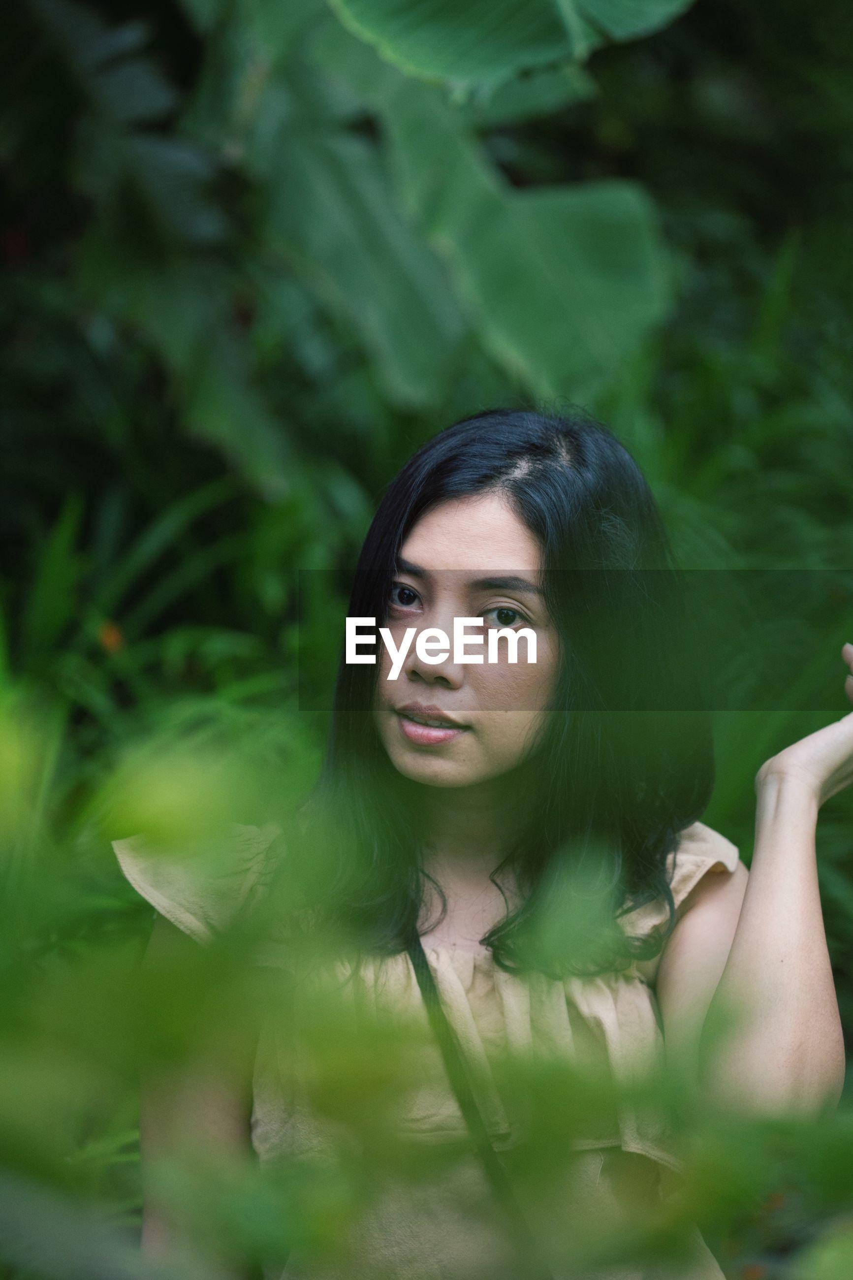 Portrait of woman amidst plants