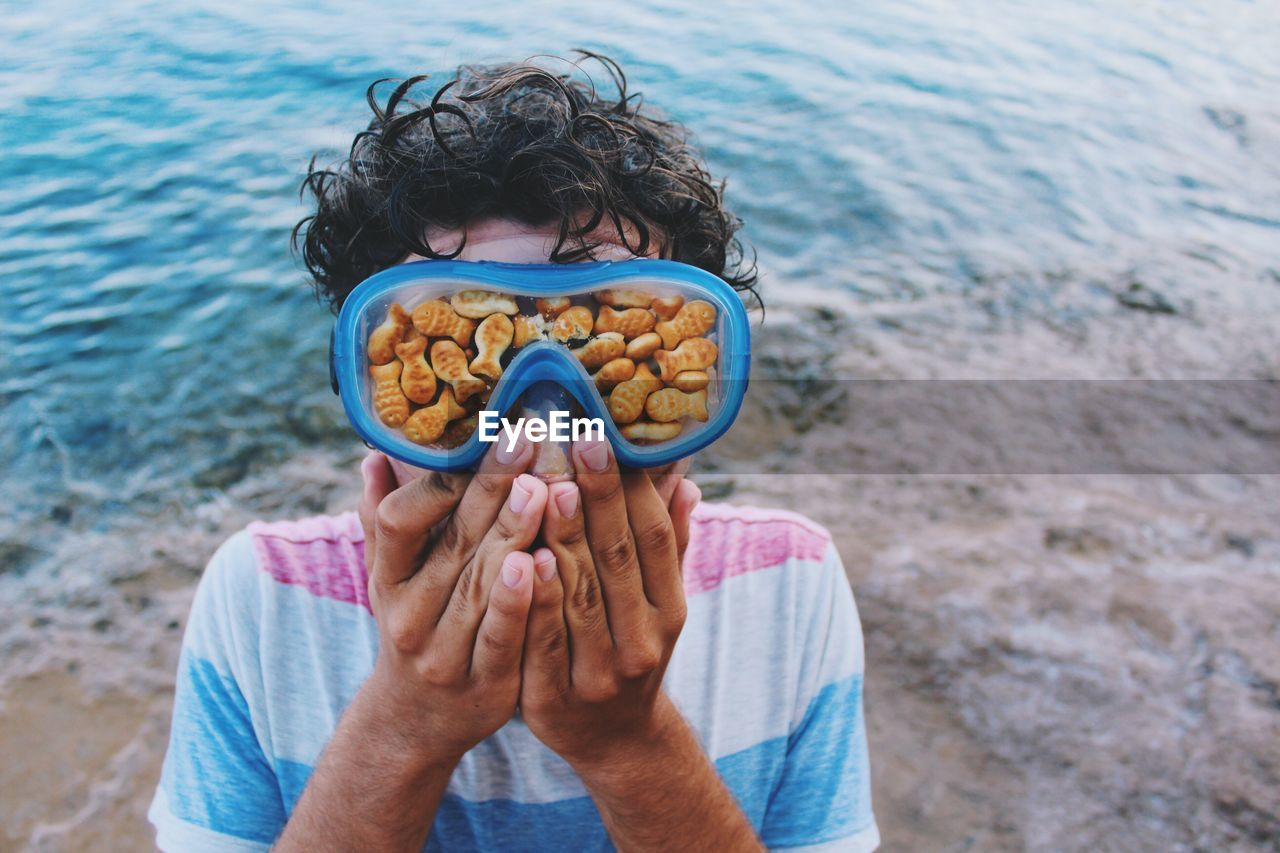 Close-Up Of Man Wearing Swimming Goggles With Fish Food At Beach