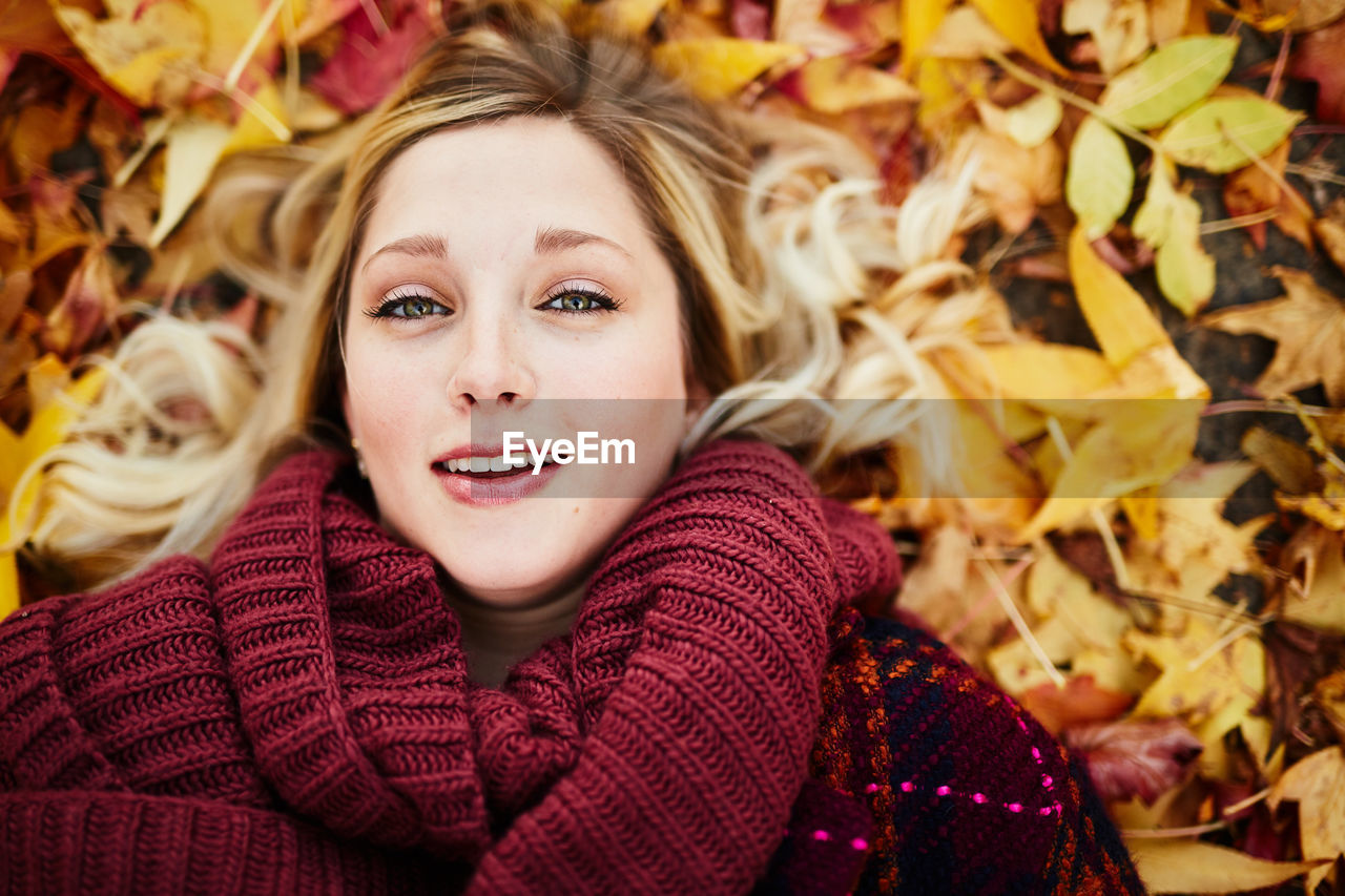 autumn, portrait, plant part, hair, leaf, one person, looking at camera, headshot, young adult, clothing, blond hair, happiness, young women, women, sweater, leaves, change, beautiful woman, smiling, warm clothing, scarf, positive emotion, outdoors, hairstyle
