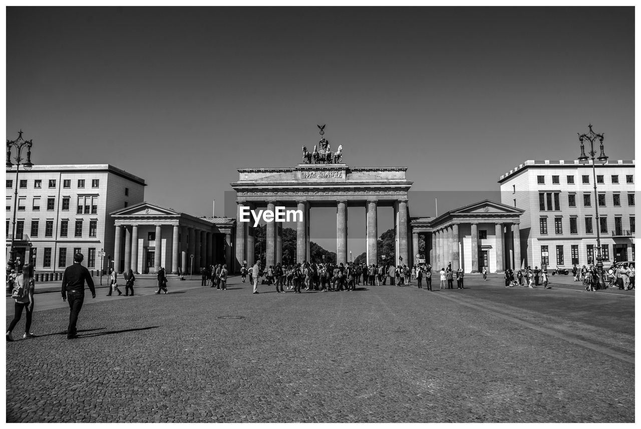 architecture, building exterior, built structure, sky, group of people, clear sky, real people, auto post production filter, transfer print, city, men, nature, large group of people, crowd, women, travel destinations, lifestyles, street, copy space, architectural column, outdoors, city gate