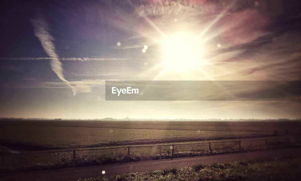 sun, sky, field, scenics, nature, tranquility, lens flare, outdoors, tranquil scene, sunlight, landscape, no people, cloud - sky, beauty in nature, sea, horizon over water, day