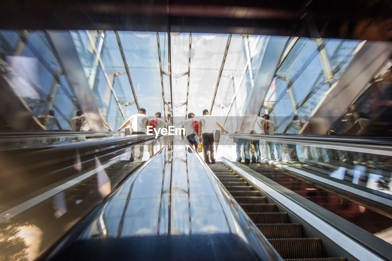 Low Angle View Of People Standing On Escalator