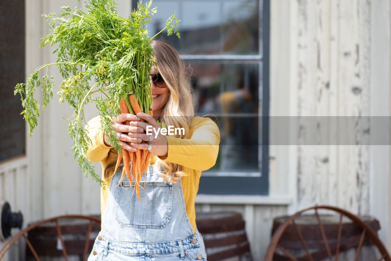 Woman holding carrots while standing against house